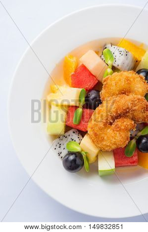 Modern cuisine style fruits salad with deep fried shrimp in ceramic dish