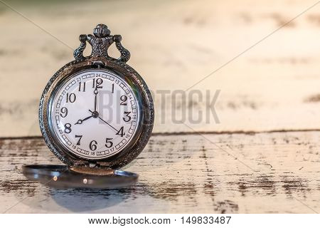 luxury vintage black pocket watch on wood table abstract for time concept with copy space