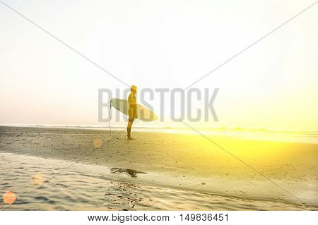 A man is standing with a surf in his hands on the sea shore wearing wet suit - Surfer looking the sea at sunrise on the beach - Extreme sport concept - Warm filter with sun halo flare