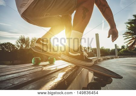 Silhouette of young man playing longboard at sunset with back lighting - Skater having fun doing extreme sport in urban contest - Freedom and sport concept - Focus on right shoe - Raw filter