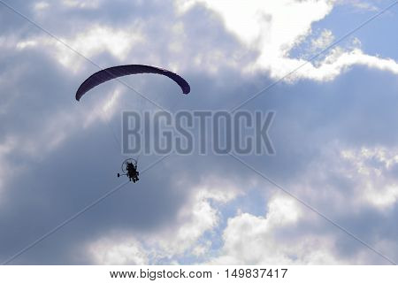 Powered paraglider aircraft flying through cloudy sky