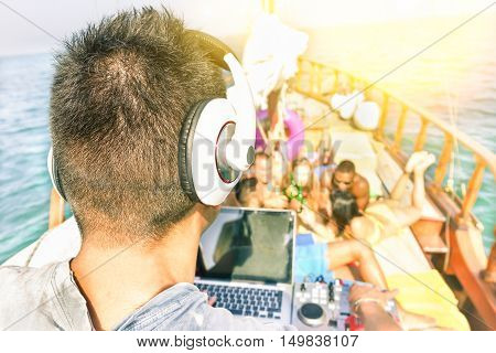Multiracial young friends having boat party at sunset - Dj playing music with blurred people in background - New music trends concept - Focus on right headphone - Warm filter with sun halo flare