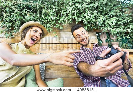 Young couple watching photos surprised on camera - Handsome lovers making funny faces looking touch screen - Travel and happiness in relation concept - Warm vintage filter