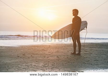 Silhouette of surfer standing on the beach waiting for waves at sunset time - Man with surfboard wearing wet suit looking sunrise - Extreme sport concept - Vintage editing