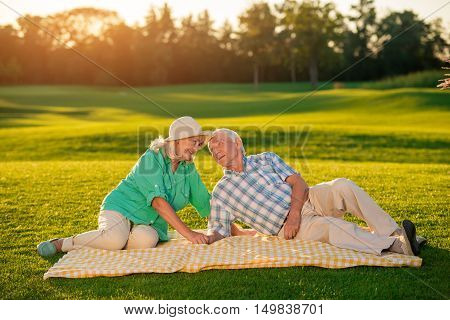 Elderly couple lying on blanket. Smiling senior man and woman. Drowning in your eyes. Didn't dream of bigger happiness.