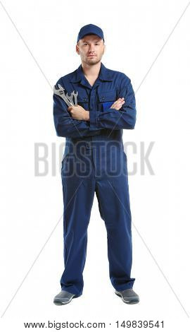 Young mechanic in uniform with crossed arms and wrenches standing, isolated on white