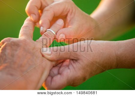 Woman puts ring on man. Hands of old couple. I won't ever leave you. Love is mutual.