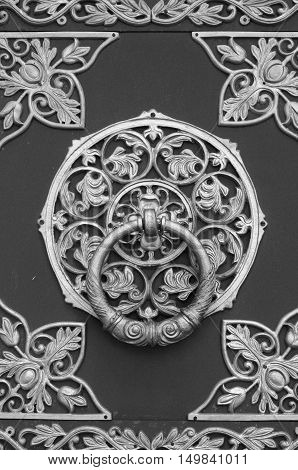 Door Orthodox Church with wrought iron ornaments. Black and white photo.
