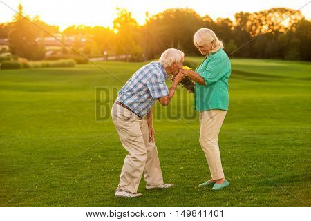 Senior man kissing woman's hand. Couple standing on a meadow. Loving heart of gentleman. Our feelings are strong.