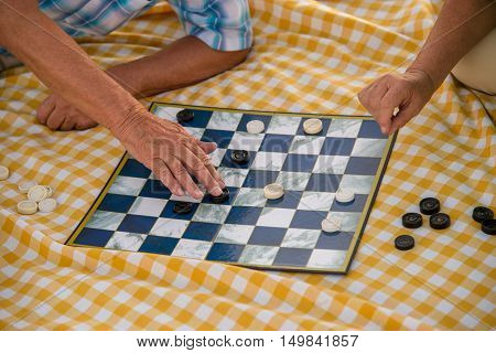 Hands of people playing checkers. Yellow checkered blanket. One step closer to victory. Show me your skills.