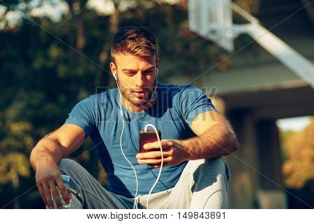 Handsome young man listening to music via smartphone and earbuds