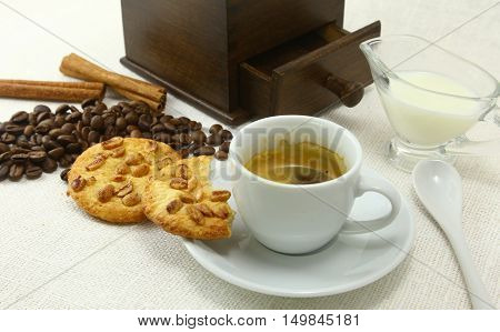 Coffee cup biscuit grinder and coffeebeans on table. poster