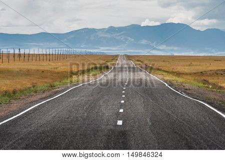 Straight road goes to horizon on background of mountains. Altay mountains, Siberia, Russia.