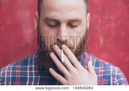 bearded young man in a flannel plaid shirt smoke cigarette