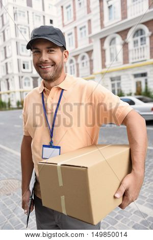 Your parcel is safe with us. Smiling deliveryman holding box while standing on street and looking at camera