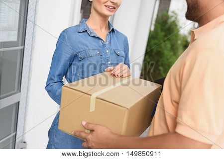 Carrying out urgent delivery. Cropped shot of smiling woman hands accepting delivery of box from deliveryman