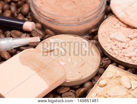 Close-up of cosmetic sponge with liquid foundation, concealers, highlighting, loose and crushed compact powder on coffee beans. Makeup products to create the perfect skin tone and complexion