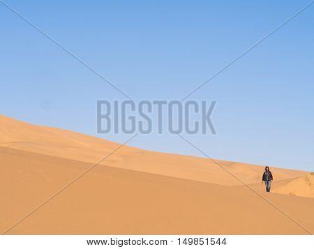 Single man walking on the Namib Desert Namibia.