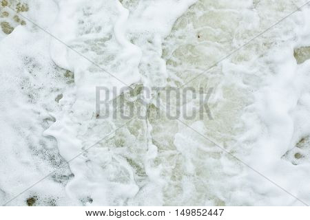 Wave action on a sandy beach causing white foam and bubbles