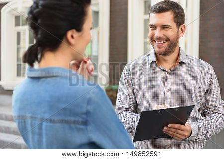 Best home for you. Smiling positive realtor standing with his client and holding clipboard while talking outdoor