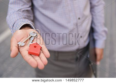 This my first home. Top view of man holding keys in his hand from new apartment, standing outdoor