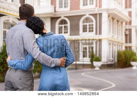 This house is our dream. Rear view of young couple standing in front of apartment complex and embracing