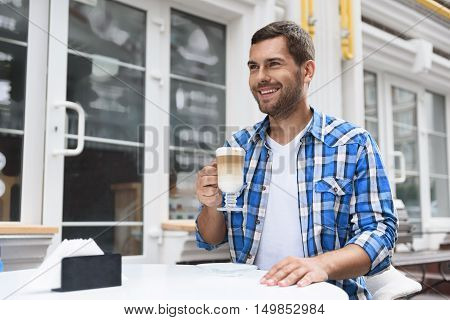 Good days start with cup of latte. Shot of young man sitting in cafe in street, holding cup of latte in his hand and smiling sincerely