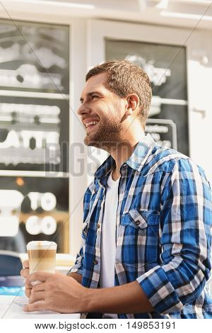 Thinking about day ahead. Side view of young man looking to side, holding cup of latte and smiling happily