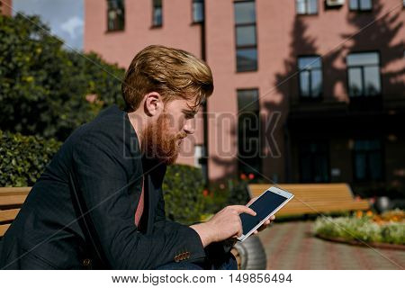 European collage student with red bearded sit on bench with tablet and read news. Serious lonly man use computer technologies to search a job.