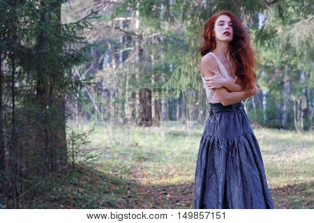 Young woman in skirt and belt poses on wind in sunny autumn forest