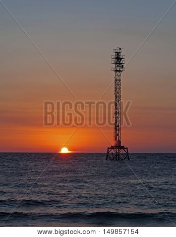 A metal tower in the ocean, at sunset. Fort De Soto, Florida