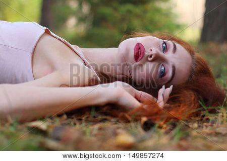 Pretty woman with red hair in jersey lies on dry foliage in autumn forest close up