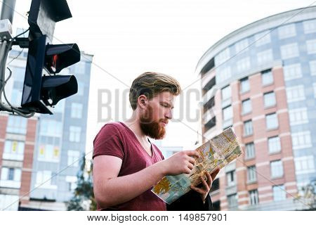Man stay under traffic light and learn map of european city to choose the way. Tourist and travel concept. Walking by foot in unfamiliar town.