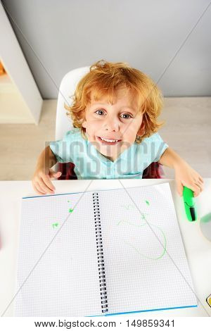 childhood and learning concept, top view of a little boy looking into camera