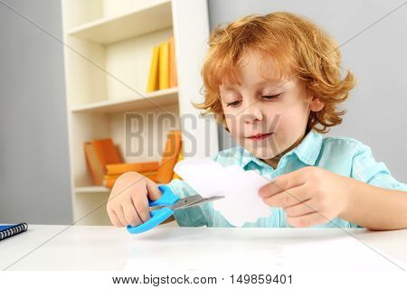 childhood and learning concept, concentrated preschooler cutting paper