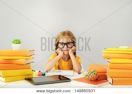 bored kid sitting in front of books and digital tablet