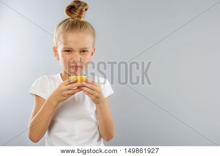 prophylaxis and health care concept, little girl tastes sour lemon