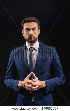 Portrait of serious businessman is looking at camera with confidence. He is standing and crossing fingers. Isolated on black background