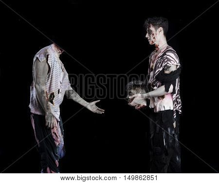 Two male zombies, one giving the head to the decapitated one's body, standing on black background