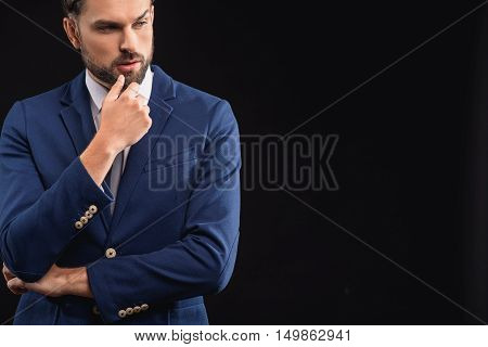 Pensive young businessman is thinking about something with concentration. He is touching chin and looking aside with seriousness. Isolated and copy space in right side