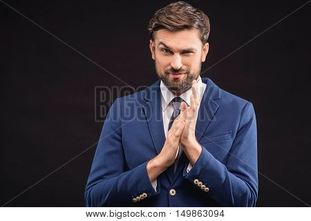 Sly young man is ready to deal with business. He is standing and rubbing his hands. Man is looking at camera with preparation. Isolated
