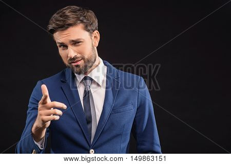 You. Successful young businessman is pointing finger forward with confidence. He is standing in expensive suit. Isolated and copy space in right side