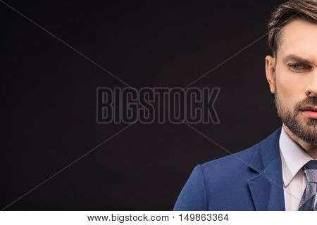 Pensive businessman is deciding serious question. He is standing and looking aside thoughtfully. Isolated and copy space in left side