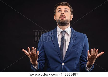 Desperate businessman is trying to solve problem. He is gesturing and looking up with hope. Isolated and copy space in left side