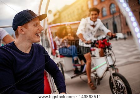 Happy young man enjoying tricycle ride in the city with friends. Teenagers enjoying holiday on tricycles.