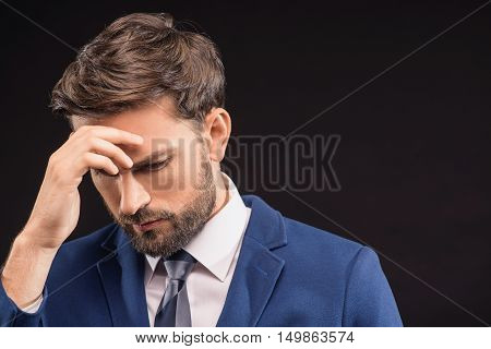 Frustrated man is experiencing business troubles. He is touching forehead and looking down pensively. Isolated and copy space in right side