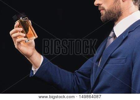 This masculine perfume is great. Confident young businessman is standing and holding bottle of cologne. Isolated