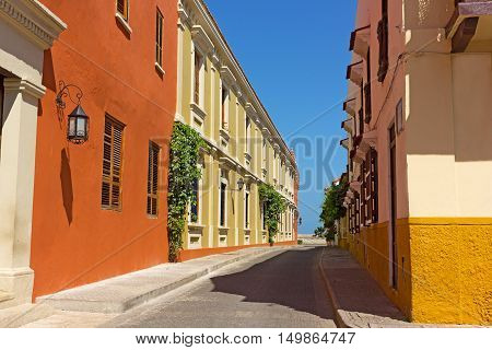 Vintage buildings on Cartagena street leading to the sea Colombia. Colorful buildings in Cartagena walled city.
