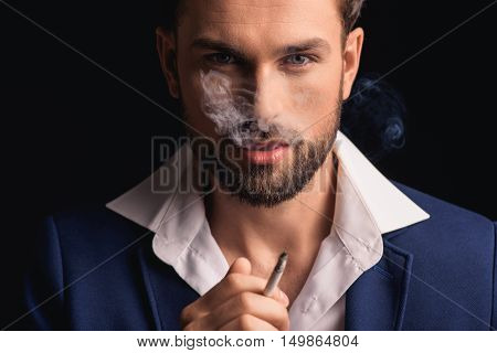 Confident businessman is exhaling smoke and looking at camera with passion. He is standing and holding cigarette. Isolated