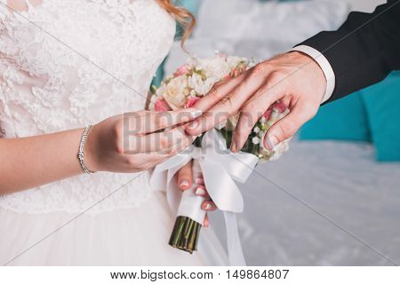 wedding rings and hands of bride and groom. young wedding couple at ceremony. matrimony. man and woman in love. two happy people celebrating becoming family